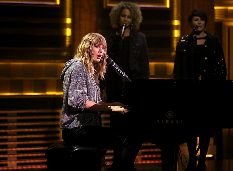 Taylor Swift sitting at a piano and singing on The Tonight Show with Jimmy Fallon, wearing a grey sweatshirt
