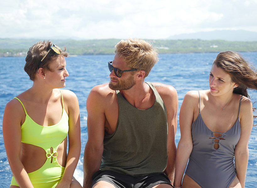 The Bachelor Canada Chris Leroux in a green tank top with two women at either side on a boat