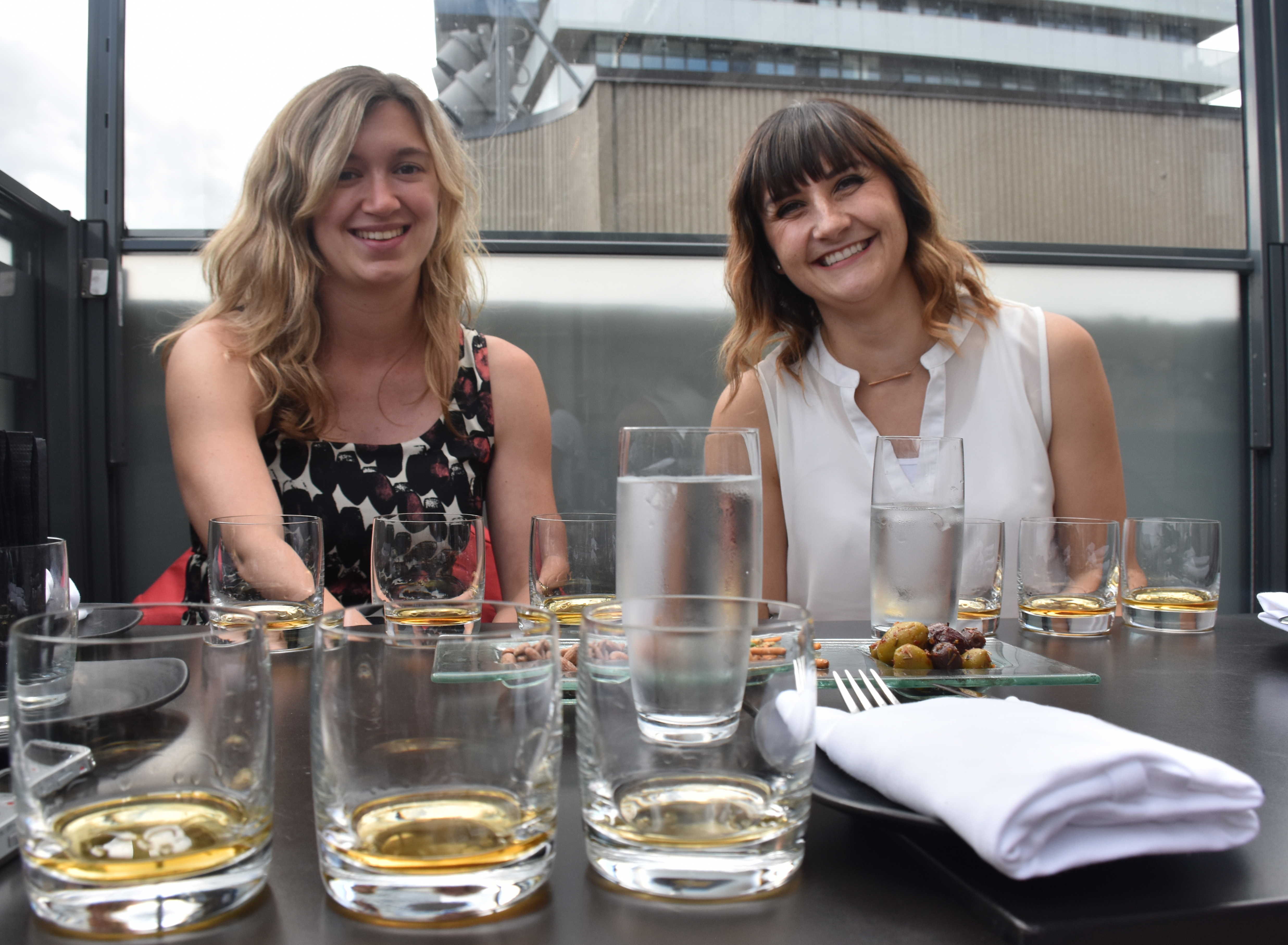Two women sit at a table with multiple tasting glasses of whiskey in front of them, they are smiling at the camera