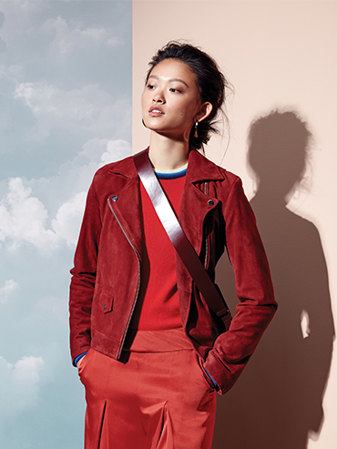 A woman wearing red clothing, including a moto jacket from Frank and Oak, Sweater from Lacoste and bag from COS.