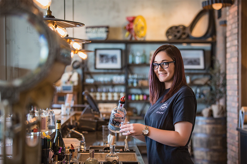 Whiskey distiller Caitlin Quinn, a distiller at Eau Claire Distillery, stands behind the bar pouring a glass of something