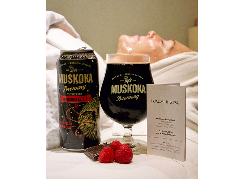 Beer skin benefits: A woman lies down on a table with muskoka beer in the forefront and raspberries in front of the cans, promo photo for a beer-infused spa treatment
