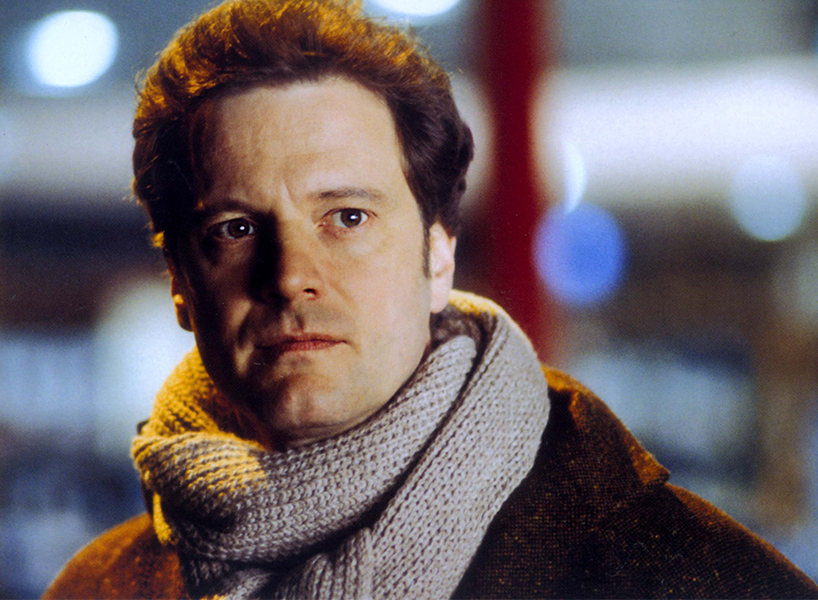 Love Actually men cast: Colin Firth wearing a scarf and a jacket stares off into the distance, looking serious, in this close-up still from the movie Love Actually