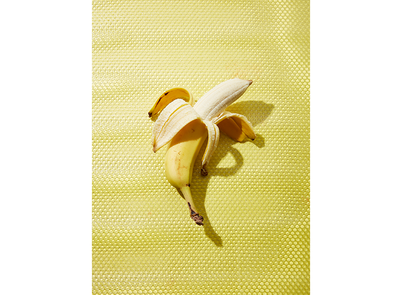 An opened banana on a yellow background