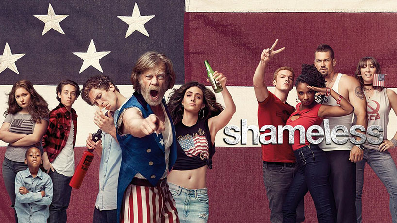 The cast of the US version of Shameless poses in front of a large American flag