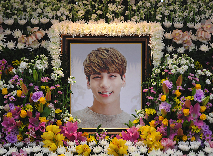 "TOPSHOT - The portrait of Kim Jong-Hyun, a 27-year-old lead singer of the massively popular K-pop boyband SHINee, is seen on a mourning altar at a hospital in Seoul on December 19, 2017. The top K-pop star bemoaned feeling ""broken from inside"" and ""engulfed"" by depression in a suicide note, it emerged on December 19, as his death sent shockwaves across K-pop fans worldwide. / AFP PHOTO / pool / CHOI Hyuk (Photo credit should read CHOI HYUK/AFP/Getty Images)"