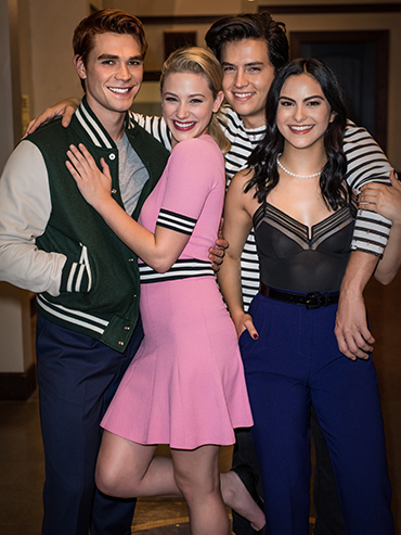 KJ Apa, Lili Reinhart, Cole Sprouse and Cami Mendes smile with their arms around each other in the hallway of Riverdale High School