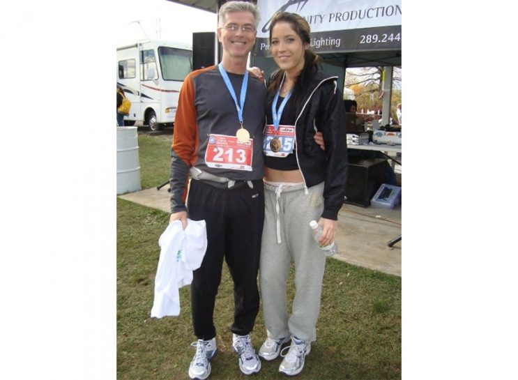 Reality of Human Trafficking: Dell and her dad. He's standing on her left and is wearing black jogging pants, a grey and orange top and a red runner's bib with the number 213 on it. She's wearing a black zip-up hoodie, black top and grey sweatpants. Her bib is blue and the number is covered with a medal.