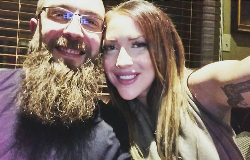Reality of Human Trafficking: A selfie of a couple sitting on a sofa. He's on the left, and has very short hair and a long beard. She is on the right and has long brown hair and a tattoo on her arm.
