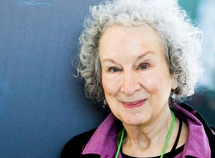 Margaret Atwood Feminism: Margaret Atwood poses for portrait session at Noir In Festival on December 6, 2017. She's standing against a grey-blue background and wearing a purple shirt and black jacket.