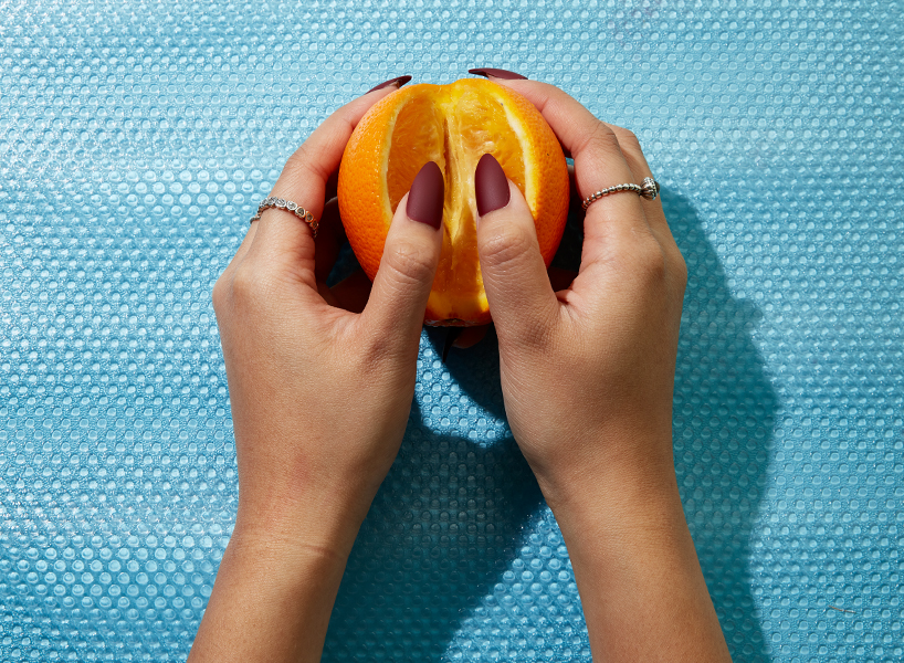A woman's hands holding an orange that's been cut open.