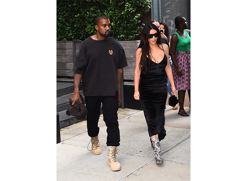 Kanye West and Kim Kardashian walk on the sidewalk in NYC