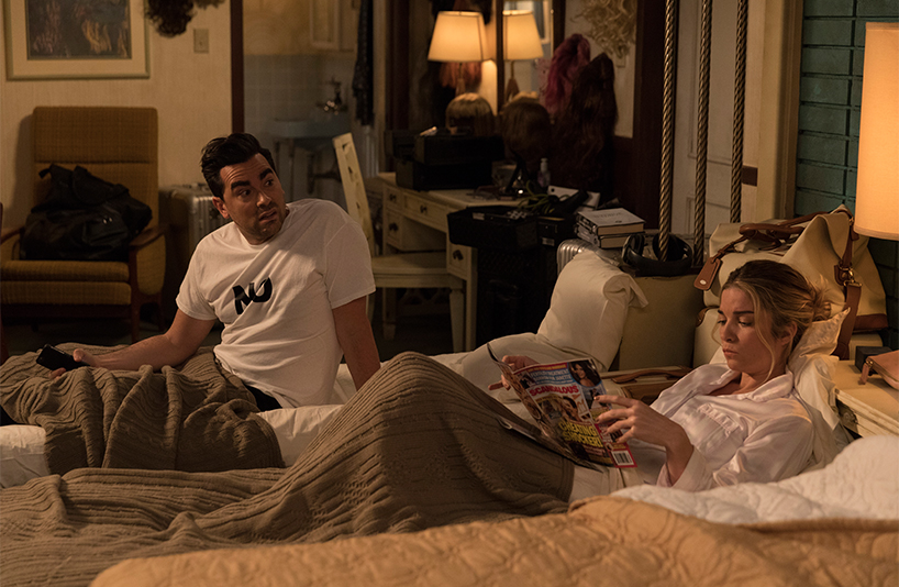 Dan Levy and Annie Murphy talk in their respective beds in a scene from Schitt's Creek