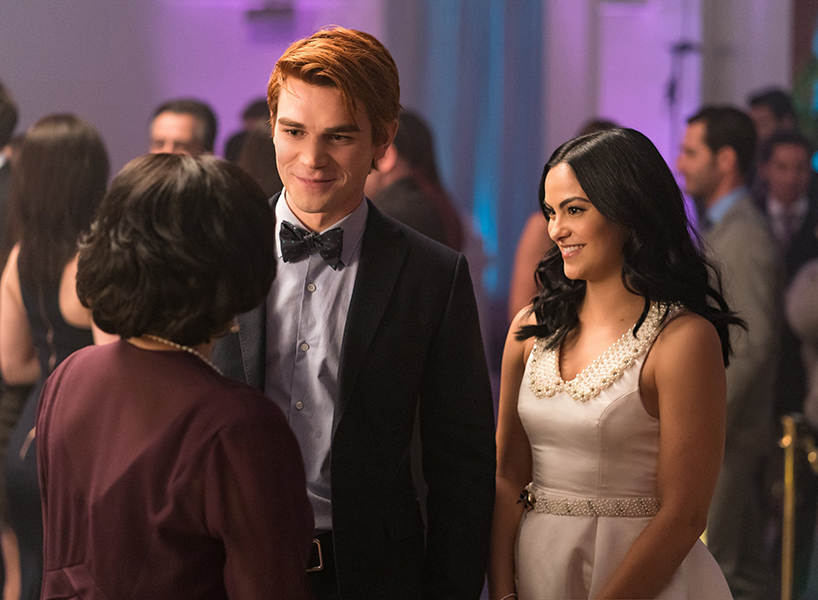 Riverdale Season 2 Episode 12: Archie and Veronica talk to a partygoer at Veronica's confirmation