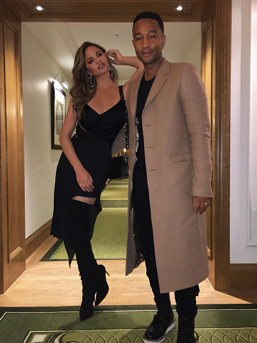 Husband and wife, singer John Legend and model Chrissy Teigen pose together in a hallway. John is wearing a long beige trench coat, and Chrissy is wearing a Black skin tight dress with thigh high black boots.