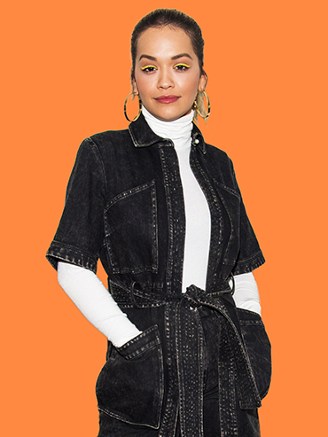 Rita Ora wears a linen jumpsuit and white turtleneck.