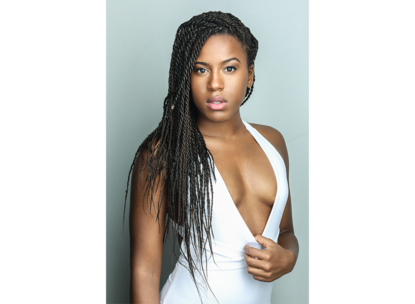 Riverdale actor Asha Bromfield posing in a white top