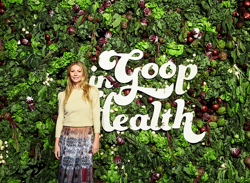 Gwyneth Paltrow poses in front of a wall of plants and vegetables at the GOOP health conference