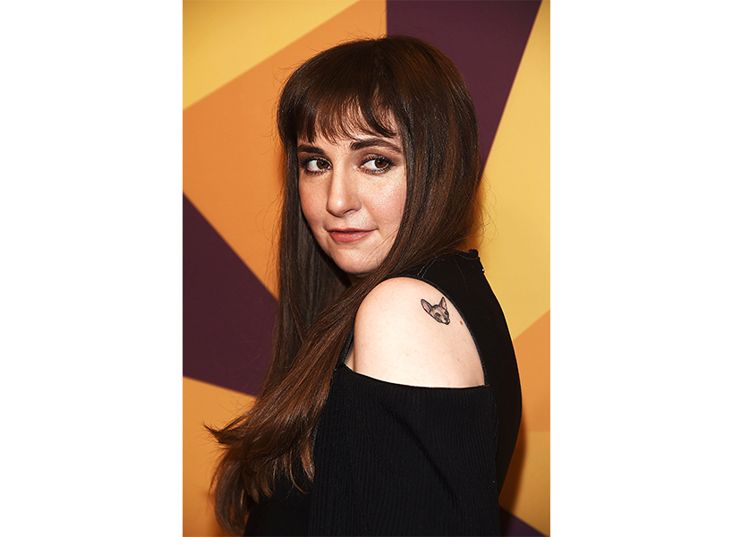 Lena Dunham where a cold-shoulder top that shows a small dog tattoo on her shoulder
