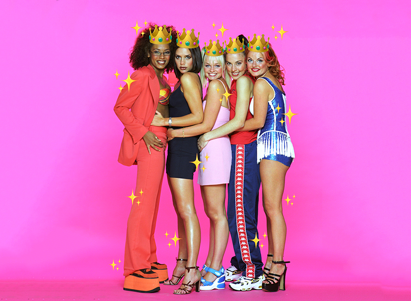 The Spice Girls hold each other and pose for a group photo against a hot pink background