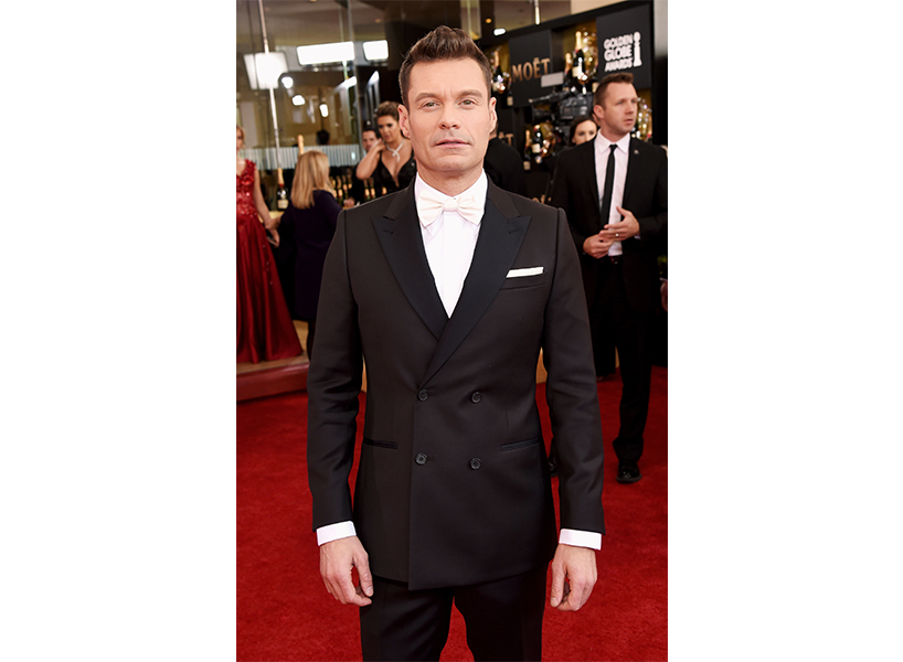 Ryan Seacrest in a tuxedo on the red carpet, he is looking at the camera and looks serious