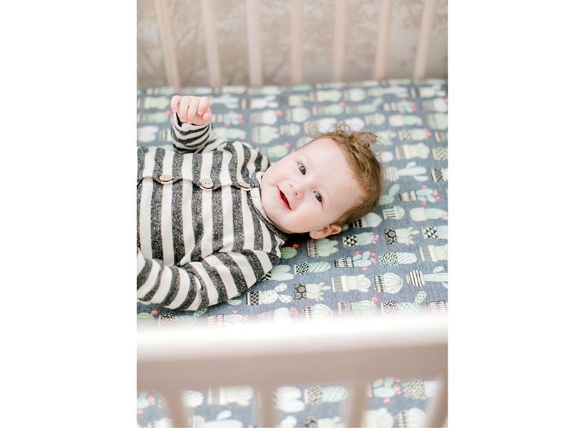 Sonny smiles in his crib wearing a striped onesie.