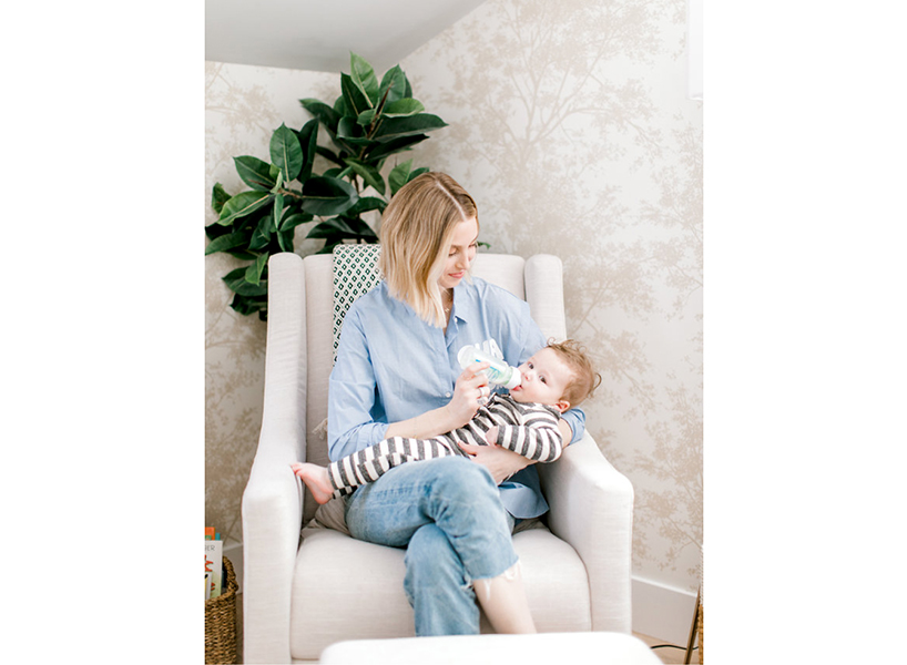 Whitney Port feeds baby Sonny with a baby bottle in a rocking chair
