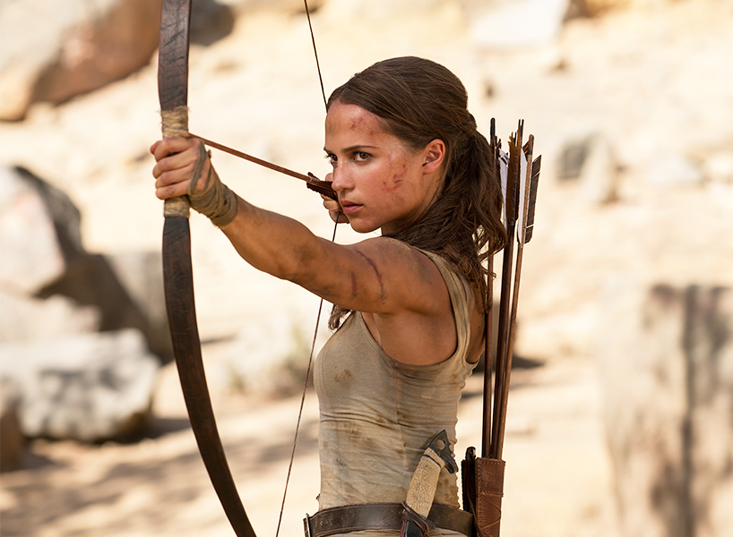Tomb Raider review: Alicia Vikander holding a bow and arrow aiming at a target in a scene from the Tomb Raider reboot