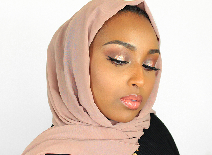 Muslim YouTube creator Aysha Abdul poses in a photo, eyes looking down wearing a pink hijab and pink eyeshadow