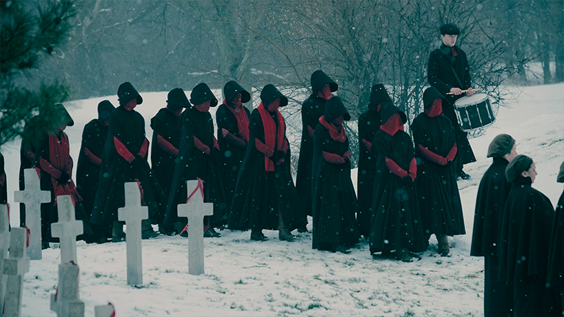 A group of women wearing black cloaks and red face masks walk through a cemetery in winter in this scene from The Handmaid's Tale season 2