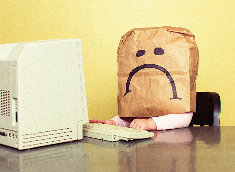 A photo of someone at a computer wearing a paper bag on their head—inline