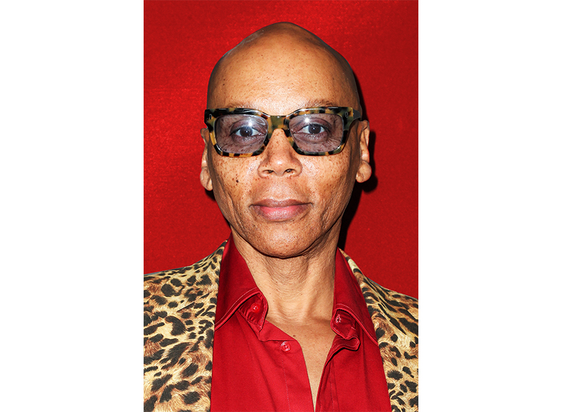 RuPaul posing in glasses and a red shirt