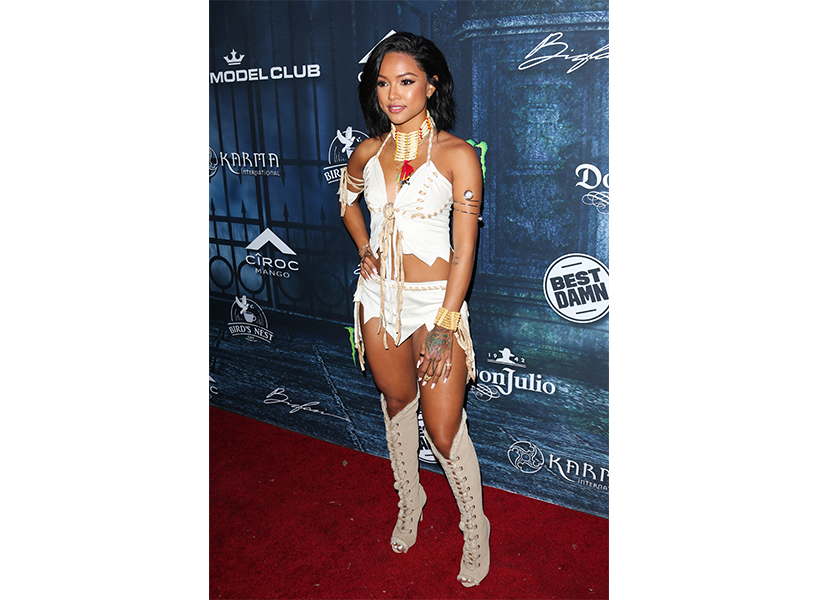 Spirit Halloween Pocahottie: Karrueche Tran poses on a red carpet for Maxim wearing a faux Indigenous costume
