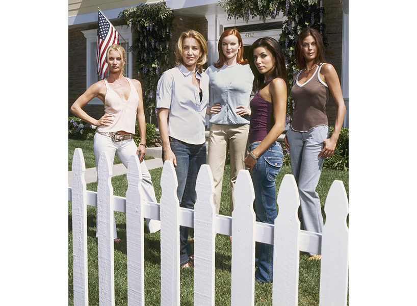 Desperate Housewives Reboot: A still from Desperate Housewives showing Eva Longoria and the rest of the cast standing on the grass behind a white picket fence staring at the camera