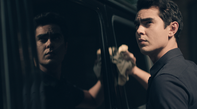 Max Minghella as Nick in the Handmaid's Tale washes a black car and looks up looking concerned