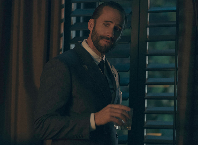Joseph Fiennes as the Commander in The Handmaid's Tale holds a glass of scotch and stands by a window in a suit