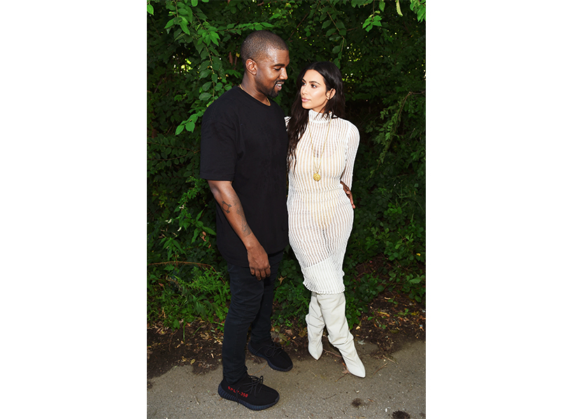 Kim Kardashian, wearing a white dress, stands next to husband Kanye West, who is wearing a black t-shirt and pants. Kim Kardashian's house has made news recently because fans got a look into the inside after Kanye tweeted out photos.
