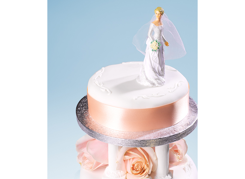 a bride topper on top of a wedding cake