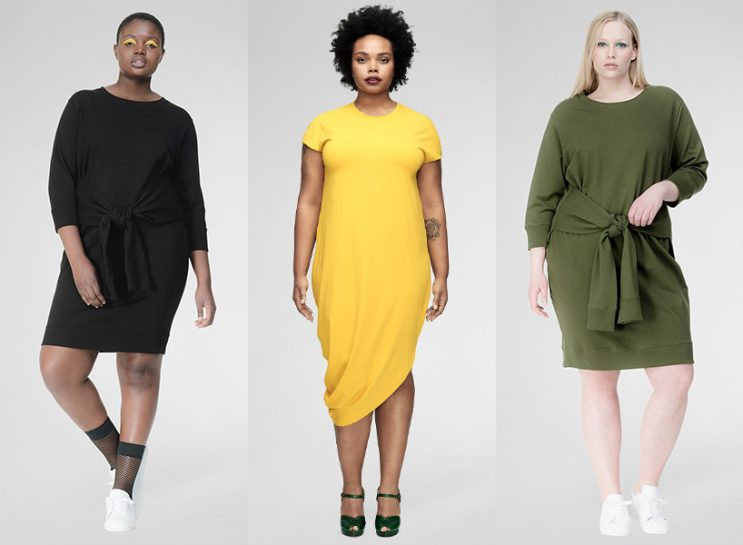 Universal Standard Extended Sizing: Three models wearing Universal Standard dresses; one is wearing a long-sleeved black, knee-length dress, one is wearing a yellow, short-sleeved dress with an asymmetrical hem and the third is wearing an olive green long-sleeved dress.