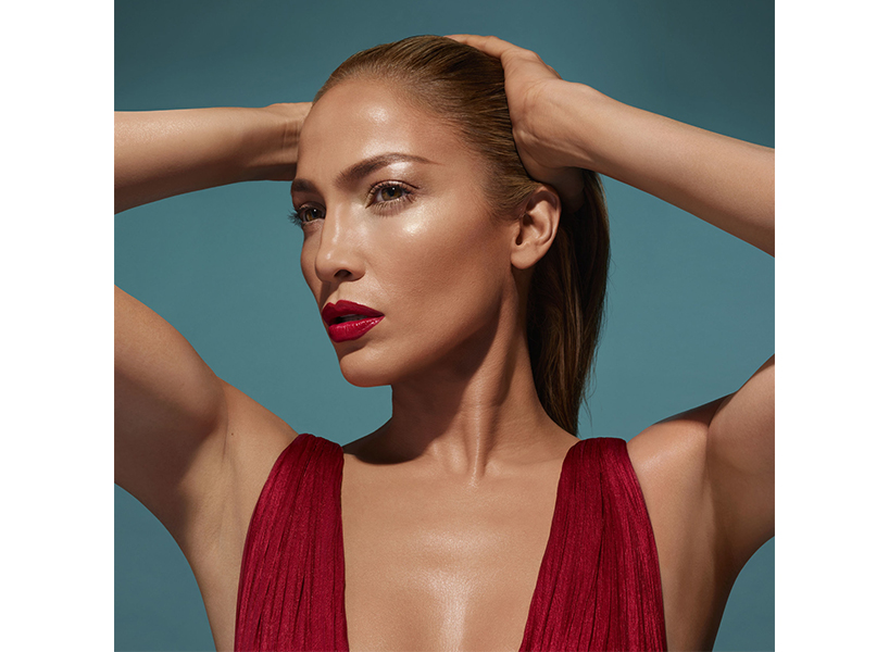 JLO Glow makeup: Jennifer Lopez poses with her hands on her hair, staring off into the distance, she is wearing a red low cut top and the photo is