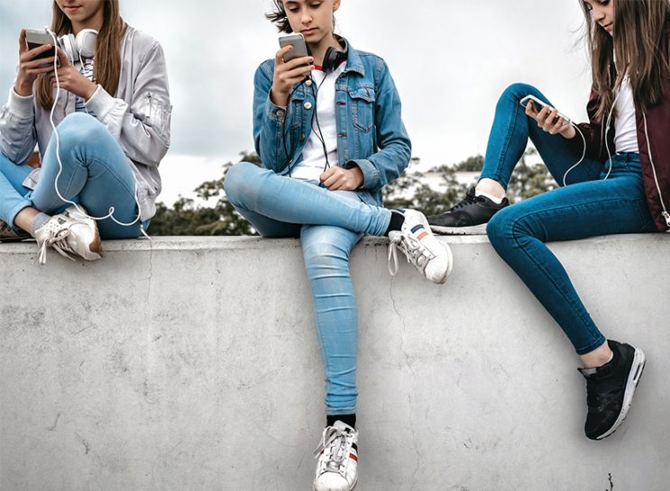 Social Media Teens: A teen girl wearing jeans and a jean jacket, sitting on a wall looking at her phone