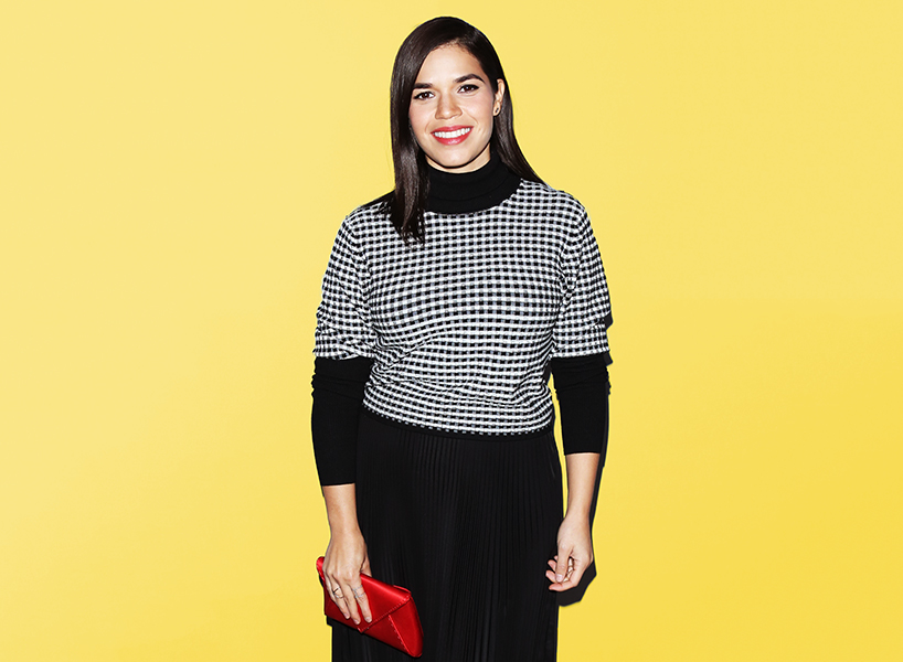 America Ferrera baby shower: America Ferrera wearing a black and white checkered shirt over a black turtle neck and smiling at the camera