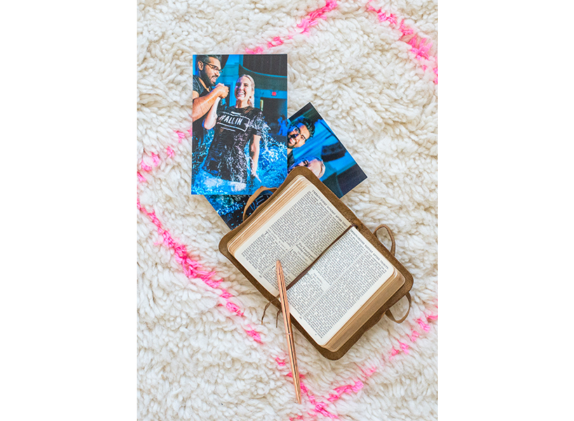 A photo of an open bible and photographs of an adult baptism on a carpet with a hot pink grid