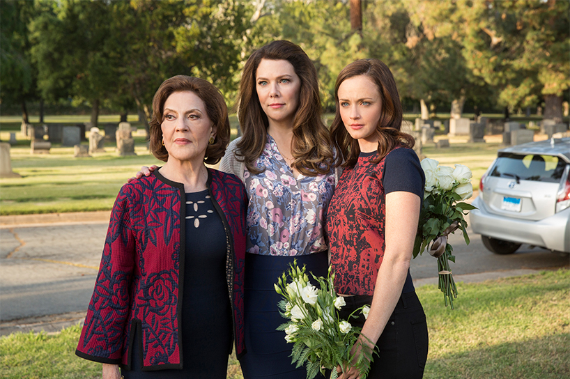 Gilmore Girls revival: The three leading ladies in Gilmore Girls stand looking serious in a cemetery holding flowers