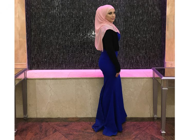 A young woman standing in front of a tiled wall, wearing a blue dress, black cardigan and pink hijab