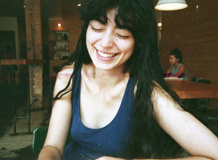A young woman sitting in a restaurant, wearing a blue tank dress. She has long black hair and bangs