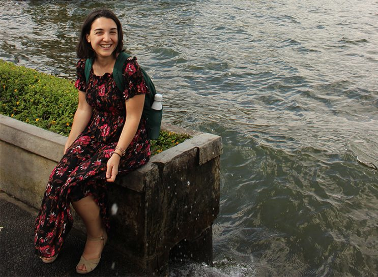 Erin, a young Turkish woman wearing a long floral dress and a green backpack. She's sitting outside beside water.