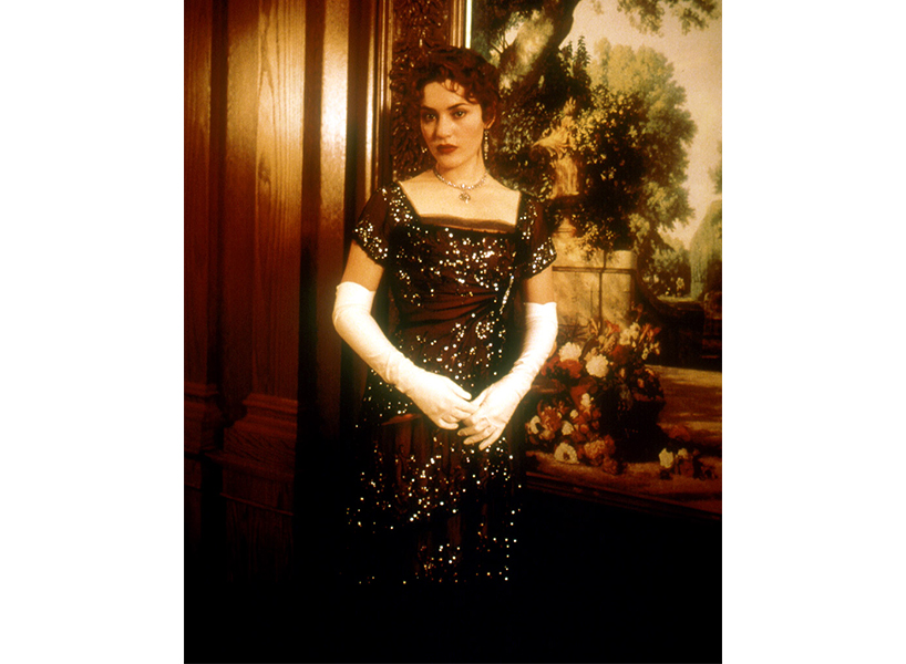 Kate Winslet poses as her character Rose in Titanic. She is wearing Rose's maroon dress with white sleeves.