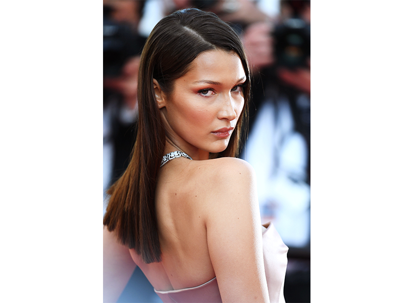 Bella Hadid wears a pink strapless gown and looks over her right shoulder at the camera.