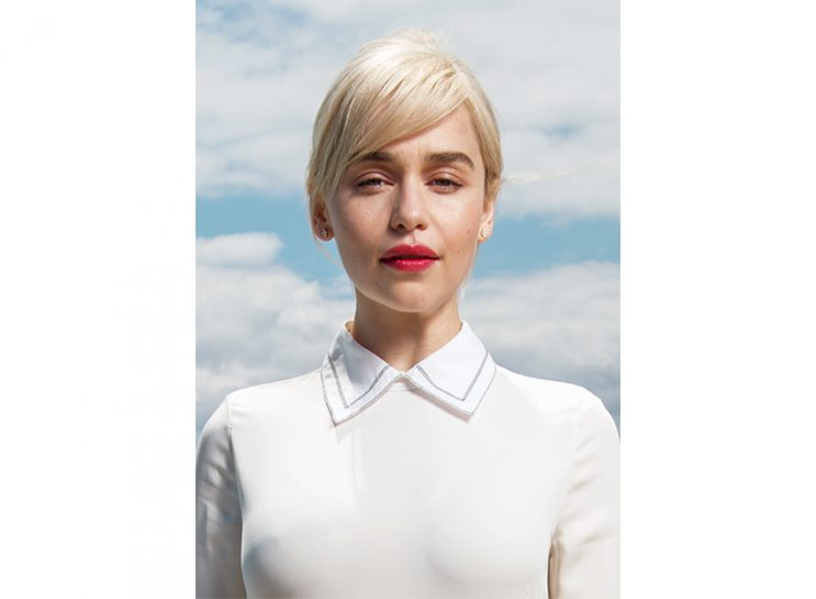 Emilia Clarke wearing a white collared button down and off-white sweater. Her hair is up and she's shown in front of a blue sky background